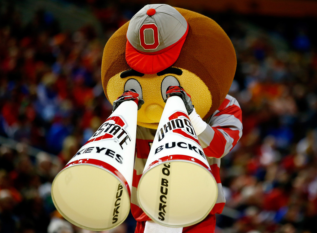 Description of . The Ohio State Buckeyes mascot, Brutus Buckeye, performs during the second round of the 2014 NCAA Men's Basketball Tournament against the Dayton Flyers at the First Niagara Center on March 20, 2014 in Buffalo, New York.  (Photo by Jared Wickerham/Getty Images)