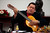 Venezuelan President Hugo Chavez plays a guitar, which was a gift from Mexican singer Vicente Fernandez, during a cabinet meeting at Miraflores Palace in Caracas September 20, 2012. Venezuelans will go to the polls for the presidential election on October 7. REUTERS/Miraflores Palace