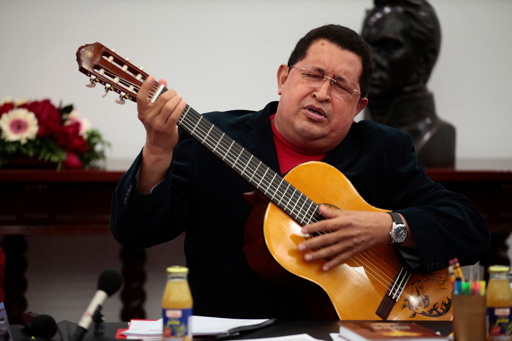 Description of . Venezuelan President Hugo Chavez plays a guitar, which was a gift from Mexican singer Vicente Fernandez, during a cabinet meeting at Miraflores Palace in Caracas September 20, 2012. Venezuelans will go to the polls for the presidential election on October 7. REUTERS/Miraflores Palace