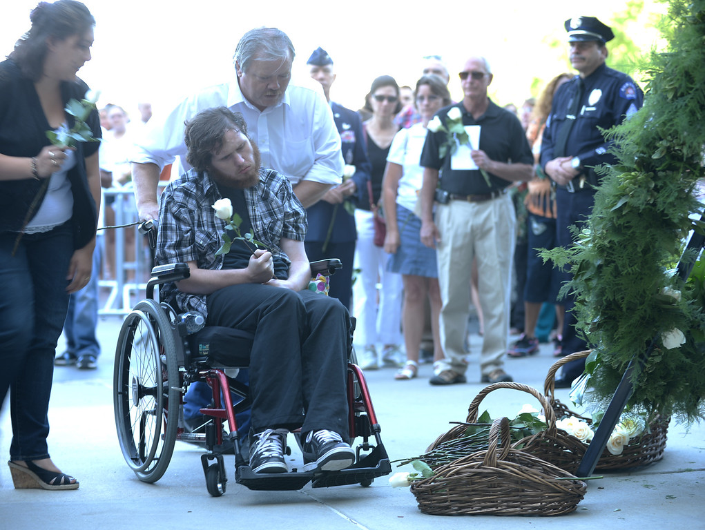 Description of . AURORA, CO. - July 20: An Aurora theater shooting victim in a wheel chair places a flower for the memorial during a day of remembrance at the Aurora Municipal Center. Aurora, Colorado. July 20, 2013. People gathered outside the Aurora Municipal Center to mark the first anniversary of the deaths of 12 people and the injury of at least 70 others in a mass shooting that forever changed an entire community. The family did not identify their names. (Photo By Hyoung Chang/The Denver Post)