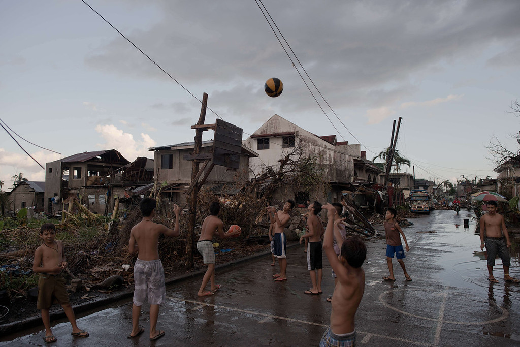 Description of . Typhoon victims play basketball with a hoop made out of wood from destroyed houses in Jaro on November 18, 2013. The United Nations has confirmed at least 4,500 killed in the disaster, which brought five-metre (16-foot) waves to Tacloban, flattening nearly everything in their path as they swept hundreds of metres across the low-lying land. NICOLAS ASFOURI/AFP/Getty Images