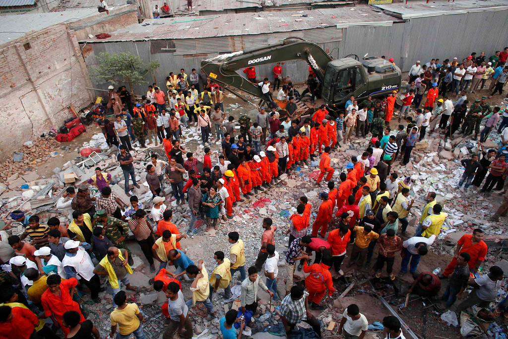 Description of . Rescue workers try to rescue trapped garment workers in the Rana Plaza building which collapsed, in Savar, 30 km (19 miles) outside Dhaka April 24, 2013. REUTERS/Andrew Biraj