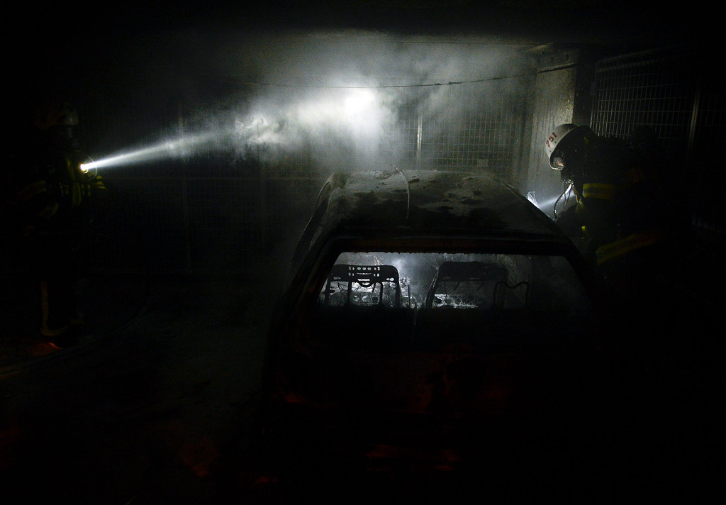 Description of . Firemen extinguish a burning car parked in an indoor garage in the Stockholm suburb of Tureberg after youths rioted in several different suburbs for a fourth consecutive night on May 24, 2013. In the suburb of Husby, where the riots began on Sunday in response to the fatal police shooting of a 69-year-old machete-wielding man, 80 percent of residents are immigrants and the unrest has highlighted Sweden's failure to integrate swathes of its immigrant population, but in this small, consensus-driven country, there was little agreement on how to solve the problem. JONATHAN NACKSTRAND/AFP/Getty Images