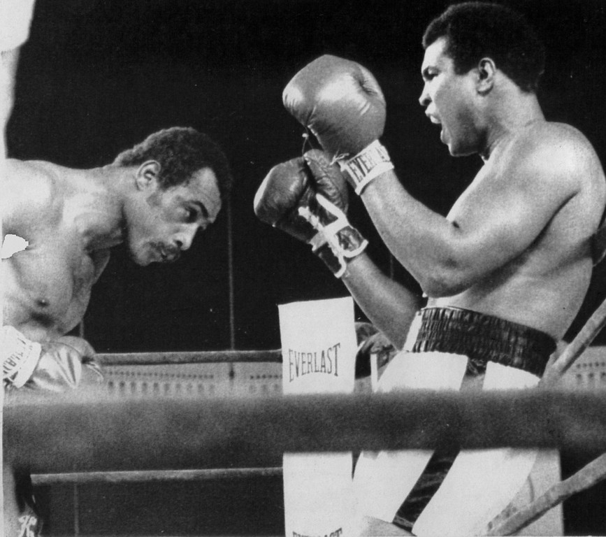 Description of . His back against the ring ropes , Muhammad Ali continues to taunt Ken Norton during their heavyweight title bout 9/28/1976. Denver Post Library photo archive