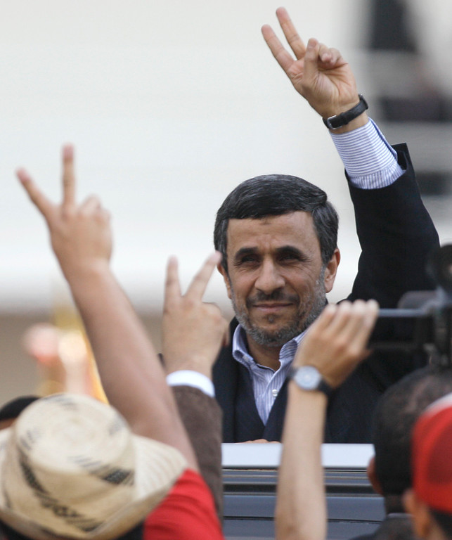 Description of . Iran's President Mahmoud Ahmadinejad makes a victory sign after attending the funeral ceremony for Venezuela's late President Hugo Chavez at the military academy in Caracas, Venezuela, Friday, March 8, 2013.   (AP Photo/Fernando Llano)