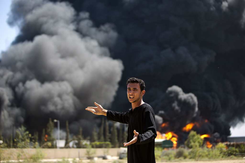 Description of . A Palestinian man reacts as flames engulf the fuel tanks of the only power plant supplying electricity to the Gaza Strip after it was hit by overnight Israeli shelling, on July 29, 2014, in the south of Gaza City. The damage of the power plant exacerbated the heavy damage to civilian infrastructure in Gaza already inflicted during the 22 days of the Israeli offensive aimed at stamping out militant rocket fire and destroying attack tunnels. AFP PHOTO/MAHMUD HAMS/AFP/Getty Images