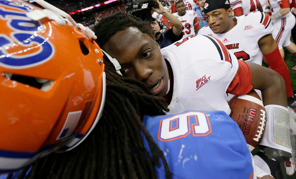 Description of . Florida defensive back Josh Evans (9) congratulates Louisville quarterback Teddy Bridgewater (5) following a 33-23 win by Louisville in the Sugar Bowl NCAA college football game Wednesday, Jan. 2, 2013, in New Orleans. (AP Photo/Dave Martin)