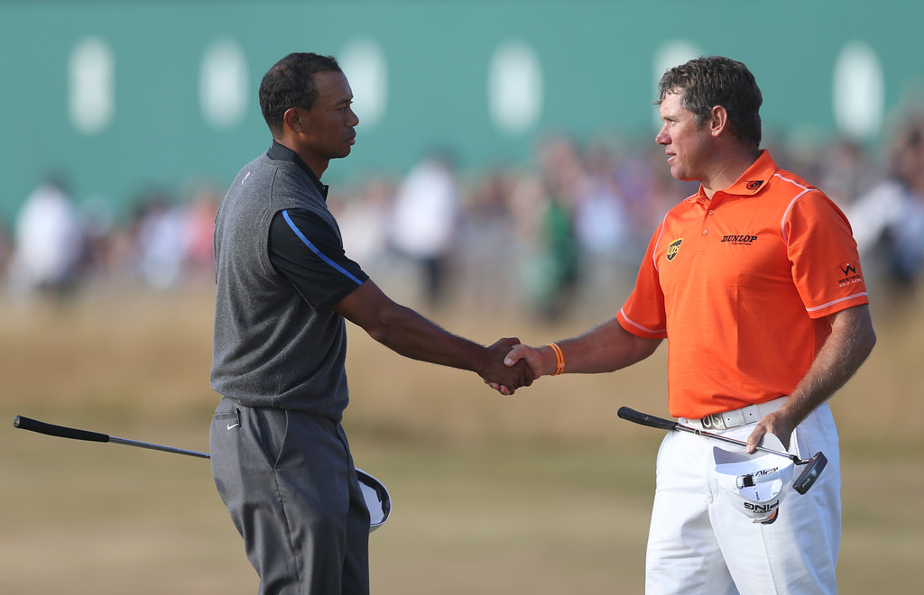 Description of . Tiger Woods of the United States, left, shakes hands with Lee Westwood of England on the 18th green after their third round of the British Open Golf Championship at Muirfield, Scotland, Saturday July 20, 2013. (AP Photo/Scott Heppell)