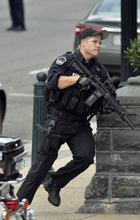 Description of . A policeman runs after shots fired were reported near 2nd Street NW and Constitution Avenue on Capitol Hill in Washington, DC, on October 3, 2013.  The US Capitol was placed on security lockdown Thursday after shots were fired outside the complex, senators said.
