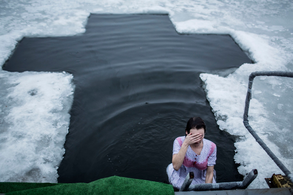 Description of . A Ukrainian woman takes a bath in the waters of lake of Sherbakova Park during the celebration of the Orthodox Epiphany in Donetsk, Ukraine. Monday, Jan. 19, 2015. Orthodox Christians celebrate the Epiphany on Jan. 19, following the old Julian calendar. (AP Photo/Manu Brabo)
