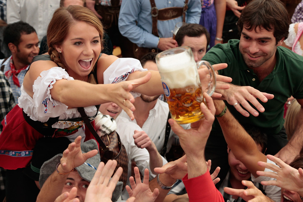 Description of . Revelers reach for the first beer mug at Hofbraeuhaus beer tent during day 1 of the Oktoberfest 2013 beer festival at Theresienwiese on September 21, 2013 in Munich, Germany. The Munich Oktoberfest, which this year will run from September 21 through October 6, is the world's largest beer fest and draws millions of visitors.  (Photo by Johannes Simon/Getty Images)