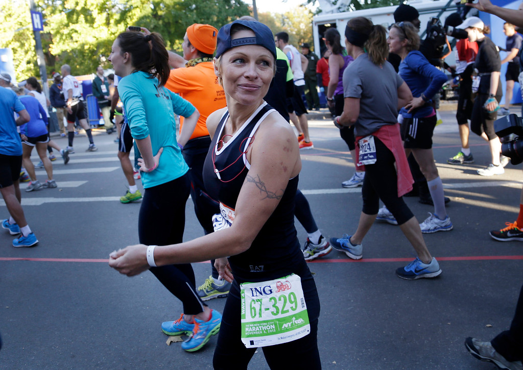 Description of . Actress Pamela Anderson smiles after crossing the finish line at the 2013 New York City Marathon in New York, Sunday, Nov. 3, 2013.  (AP Photo/Seth Wenig)