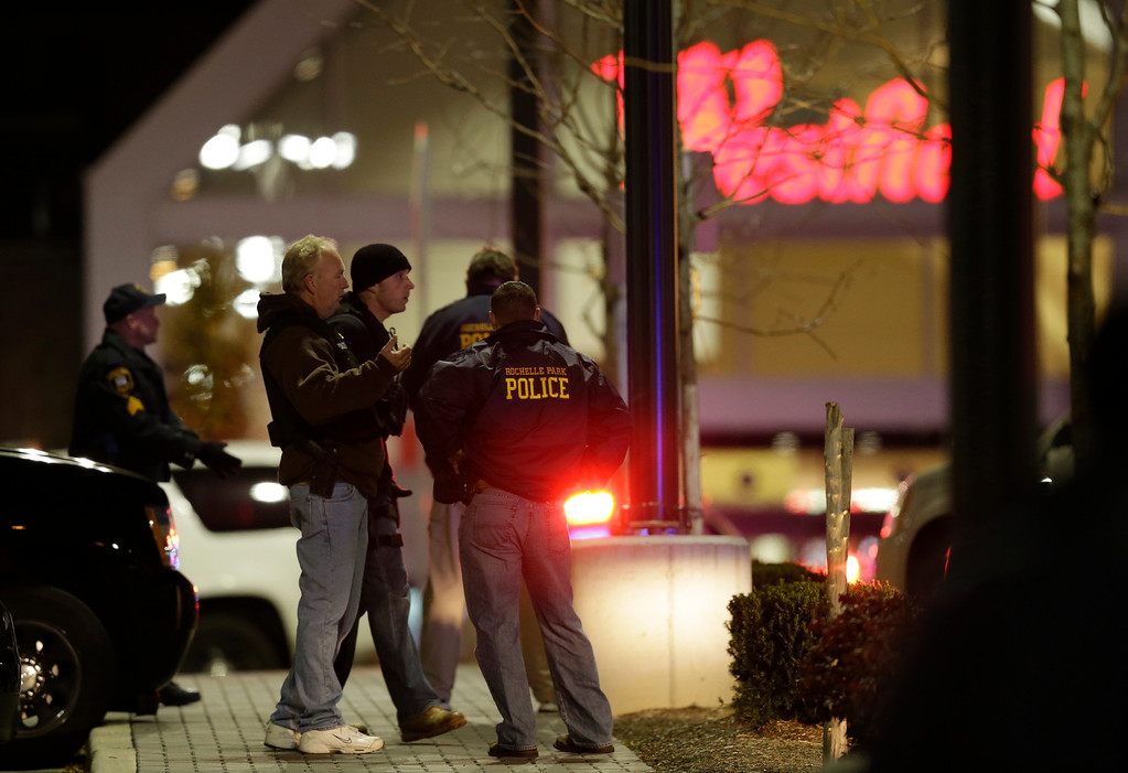 Description of . Officials stand in the parking lot of the Garden State Plaza Mall following reports of a shooter, Monday, Nov. 4, 2013, in Paramus, N.J. Hundreds of law enforcement officers converged on the mall Monday night after witnesses said multiple shots were fired there. (AP Photo/Julio Cortez)