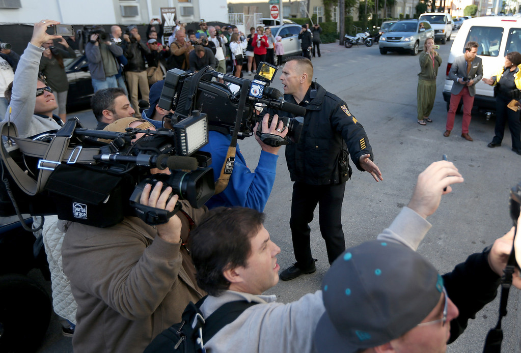 . A Miami Beach Police officer tells people to get back to make room for a van carrying Justin Bieber from the Miami Beach Police station to jail on January 23, 2014 in Miami Beach, Florida. Justin Bieber was charged with drunken driving, resisting arrest and driving without a valid license after Miami Beach Police found the pop star street racing on Thursday morning.  (Photo by Joe Raedle/Getty Images)