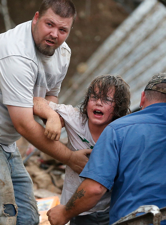 Description of . In this May 20, 2013, file photo, a child calls to his father after being pulled from the rubble of the Tower Plaza Elementary School following a tornado in Moore, Okla. (AP Photo Sue Ogrocki, File)