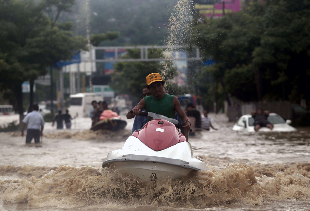 Description of . A man carries residents on a jet ski in Acapulco, Guerrero state, Mexico, after heavy rains hit the area on September 16, 2013. Hurricane Ingrid weakened to tropical storm strength as it made landfall on the northeastern coast in the morning while the Pacific coast was reeling from the remnants of Tropical Storm Manuel, which dissipated after striking on the eve. Thousands of people were evacuated on both sides of the country as the two storms set off landslides and floods that damaged bridges, roads and homes.   Pedro PARDO/AFP/Getty Images