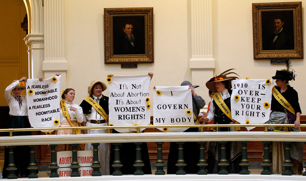 Description of . Protesters hold signs in the rotunda of the State Capitol at a protest before the start of a special session of the Legislature in Austin, Texas July 1, 2013. When the Texas Legislature convenes on Monday for a second special session, the Republican majority will seek to do what it couldn't pull off in the first: Pass sweeping abortion restrictions.  REUTERS/Mike Stone