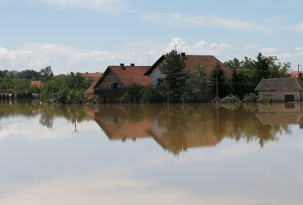 Description of . Houses reflected in a flooded area in Obrenovac, some 30 kilometers (18 miles) southwest of Belgrade, Serbia, Monday, May 19, 2014. Belgrade braced for a river surge Monday that threatened to inundate Serbia's main power plant and cause major power cuts in the crisis-stricken country as the Balkans struggle with the consequences of the worst flooding in southeastern Europe in more than a century. (AP Photo/Darko Vojinovic)