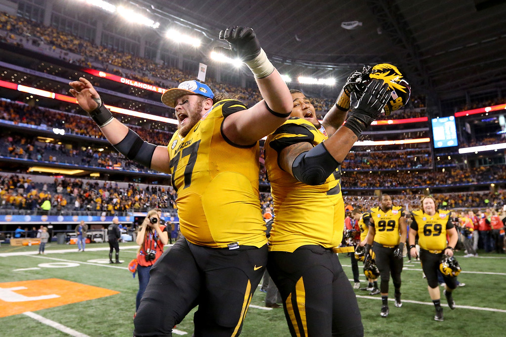 Description of . ARLINGTON, TX - JANUARY 03:  Evan Boehm #77 and Lucas Vincent #96 of the Missouri Tigers celebrates the Tigers 41-31 victory against the Oklahoma State Cowboys during the AT&T Cotton Bowl on January 3, 2014 in Arlington, Texas.  (Photo by Ronald Martinez/Getty Images)