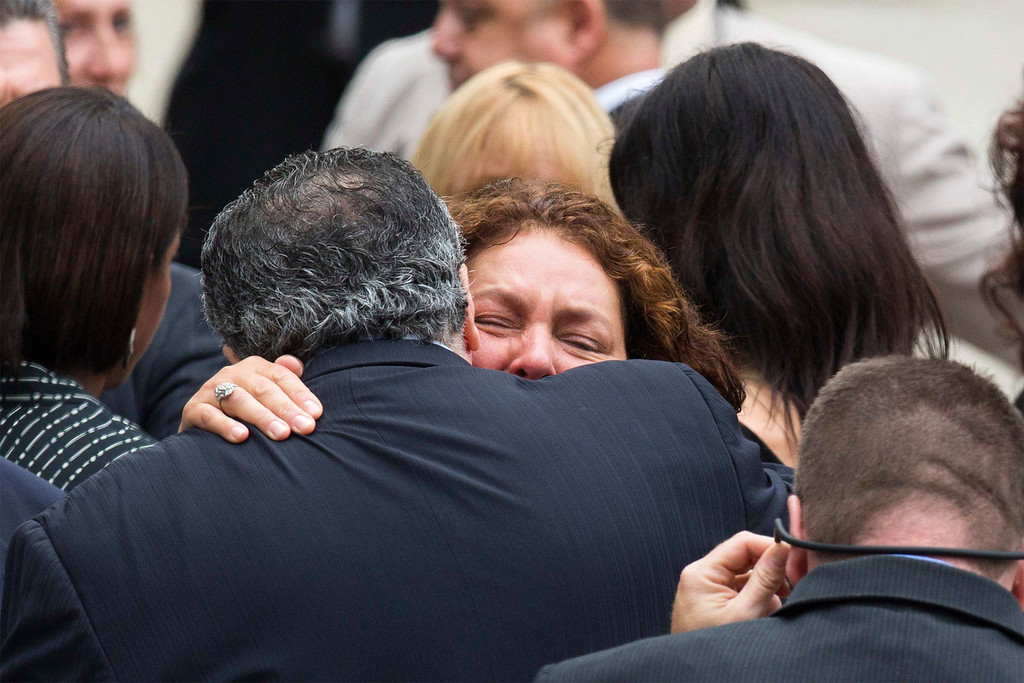 Description of . Actress Aida Turturro embraces a fellow mourner as she arrives for the funeral services of James Gandolfini outside the Cathedral Church of Saint John the Divine in New York June 27, 2013.  REUTERS/Lucas Jackson