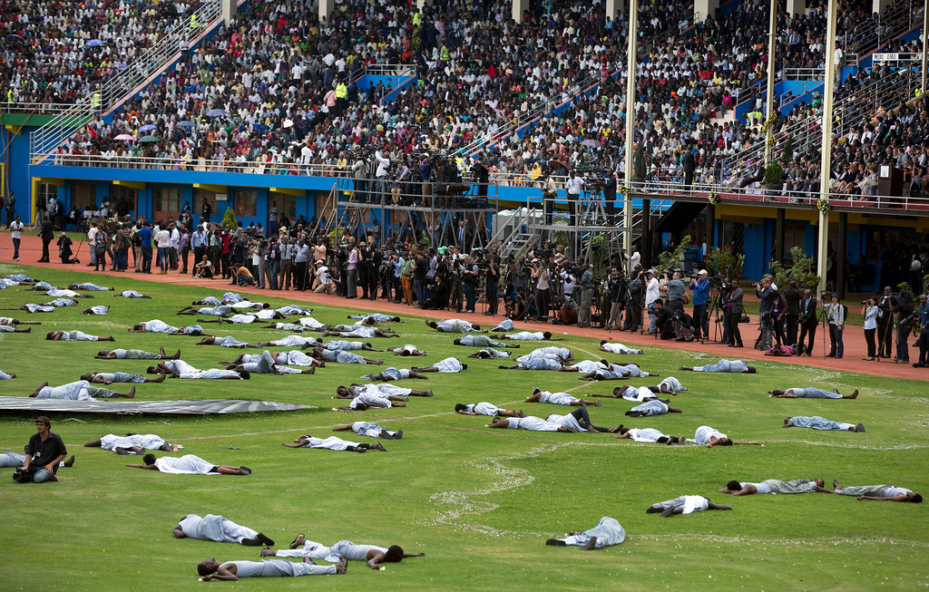 Description of . Performers re-enact the events at a public ceremony to mark the 20th anniversary of the Rwandan genocide, at Amahoro stadium in Kigali, Rwanda Monday, April 7, 2014.  (AP Photo/Ben Curtis)
