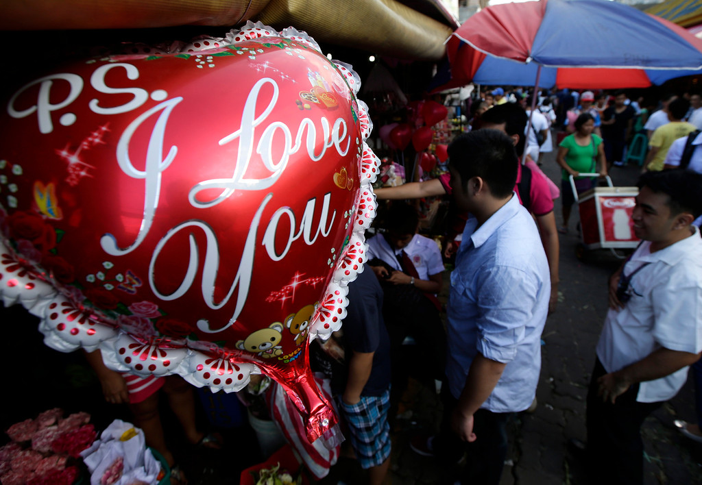 Description of . Filipinos flock to the flower street called Dangwa to buy flowers for their loved ones in celebration of Valentine's Day Thursday Feb. 14, 2013 in Manila, Philippines. Business is brisk at this flower street and flower shops around Manila with red roses being the most popular among the buyers. (AP Photo/Bullit Marquez)