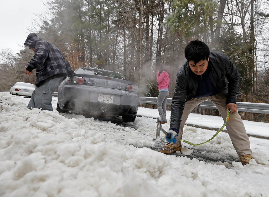 Description of . Passerby Leo Cruz, left, helps Julian Ramirez, right, dig Ramirez\'s car from the frozen roadside after abandoning the car overnight during the storm in Chapel Hill, N.C., Thursday, Feb. 13, 2014. The National Weather Service issued a winter storm warning lasting into Thursday covering 95 of the state\'s 100 counties. (AP Photo/Gerry Broome)