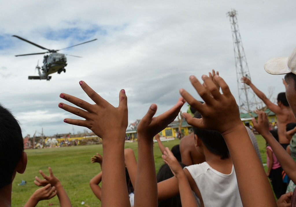 Description of . Residents wave to a US navy seahawk helicopter which dropped off relief goods in the town of Giporlos, Eastern Samar province, central Philippines on November 16, 2013. Spearheaded by a US aircraft carrier group, foreign relief efforts have stepped up a gear in the storm-devastated Philippines eight days after Super Typhoon Haiyan left thousands dead and millions homeless. AFP PHOTO/TED ALJIBE/AFP/Getty Images