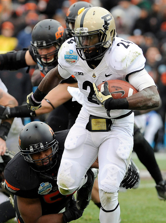 Description of . Purdue running back Akeem Shavers (24) looks for running room around Oklahoma State linebacker Ryan Simmons, bottom, during the first half of the Heart of Dallas Bowl NCAA college football game, Tuesday, Jan. 1, 2013, in Dallas. (AP Photo/Matt Strasen)