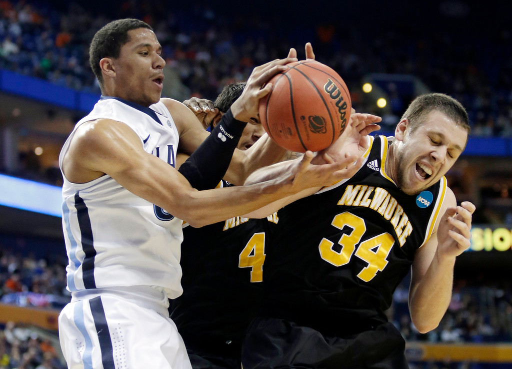 Description of . Villanova's Josh Hart, left, fights for control of the ball with Milwaukee's Malcolm Moore, center, and Austin Arians, right, during the first half of a second-round game in the NCAA college basketball tournament in Buffalo, N.Y., Thursday, March 20, 2014. (AP Photo/Nick LoVerde)