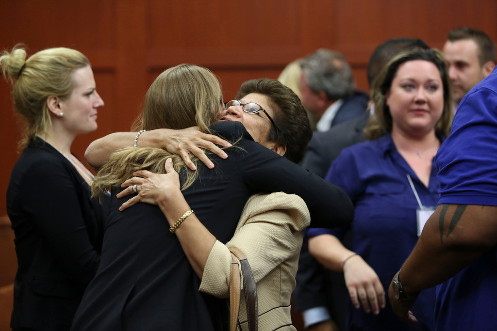 Description of . George Zimmerman's family celebrates after the jury found him not guilty in the 2012 shooting death of Trayvon Martin at the Seminole County Criminal Justice Center in Sanford, Florida, July 13, 2013. Zimmerman was acquitted of all charges on Saturday for the fatal shooting of unarmed black teenager Trayvon Martin in this central Florida town in February of last year.  REUTERS/Gary W. Green/Pool
