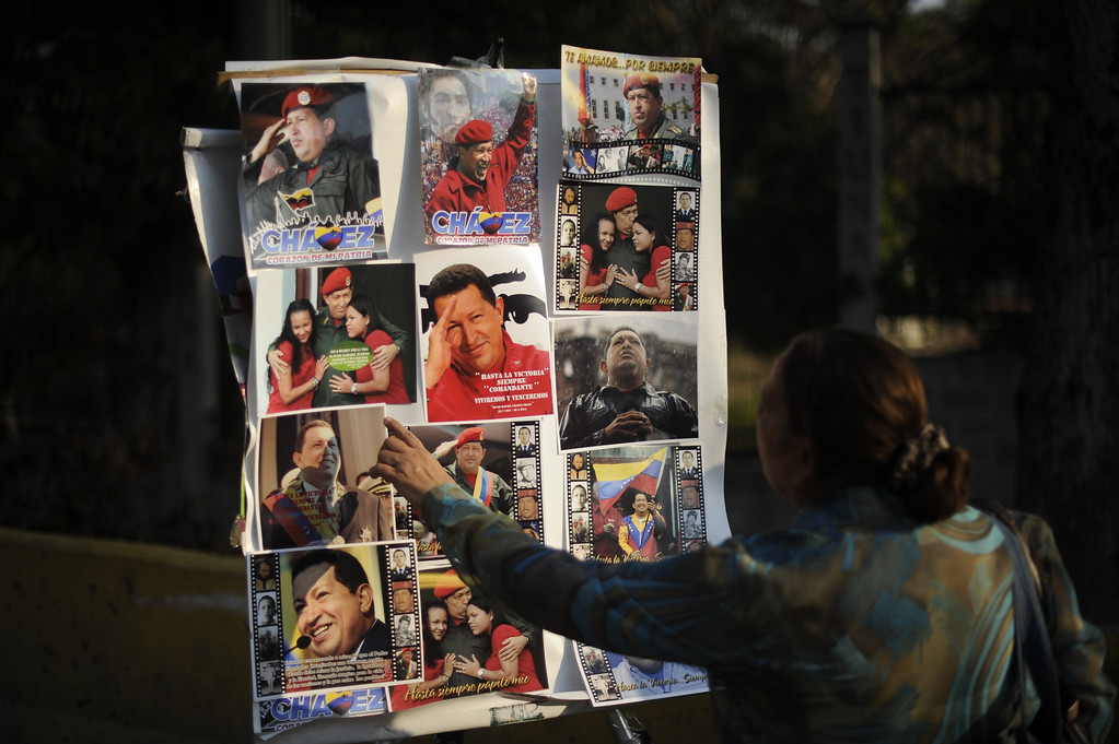 Description of . A woman points at pictures of late Venezuelan President Hugo Chavez in Caracas, on March 8, 2013.   AFP PHOTO/Eitan  ABRAMOVICH/AFP/Getty Images