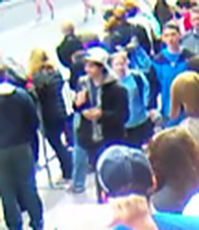 Description of . This image taken from a video released by the FBI on April 18, 2013 shows a man wearing a white cap walking along the route of the Boston Marathon on April 15. The man and one other are being sought by the FBI in connection with the marathon bombing that killed three. The US Federal Bureau of Investigation (FBI) released the photos and videos of two men sought as suspects in the Boston bombings, urging the public to help identify them.
