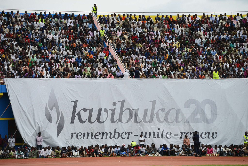 ". Rwandans gather under a banner, with writing in Kinyarwanda reading ""Remember 20\"", at the Amahoro stadium in Kigali on April 7,2014, during a ceremony marking the 20th anniversary of Rwanda\'s genocide. Rwanda on April 7 held solemn commemorations marking the 20th anniversary of the genocide, with many survivors overcome with grief as they relived the trauma of the massacres that left nearly a million dead. The events also bore reminders of festering anger, as a major diplomatic row broke out over renewed allegations of French complicity in the genocide.  AFP PHOTO / SIMON MAINA/AFP/Getty Images"