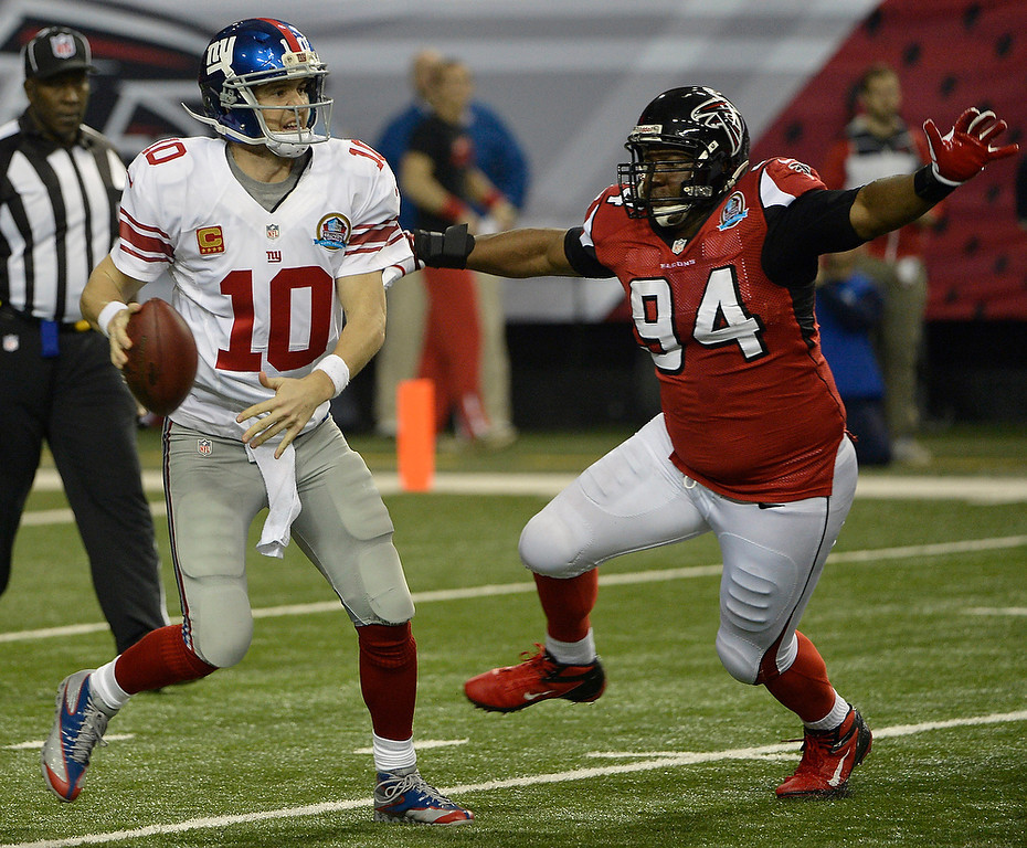 Description of . New York Giants quarterback Eli Manning (10) looks for a receiver as Atlanta Falcons defensive tackle Peria Jerry (94) defends during the first half of an NFL football game, Sunday, Dec. 16, 2012, in Atlanta. (AP Photo/Rich Addicks)