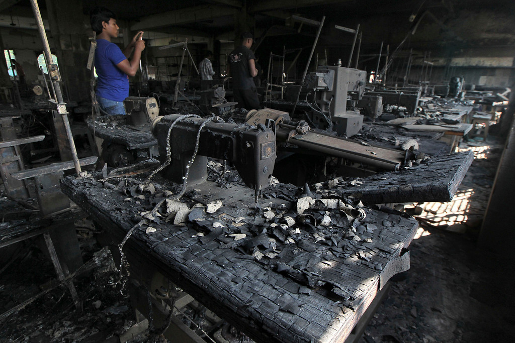 Description of . In this Monday, Nov. 26, 2012 file photo, a man takes photographs inside a burned out garment factory on the outskirts of Dhaka, Bangladesh. The blaze at the factory killed 112 workers. (AP Photo/File)