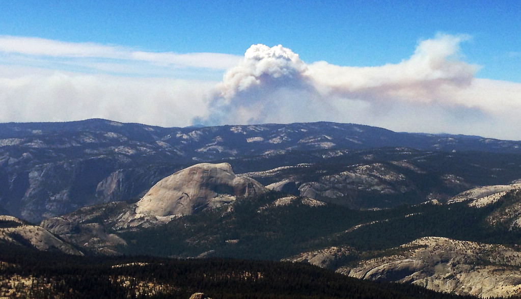 Description of . Smoke clouds from the Rim Fire in the western Sierra Nevada loom up some 20 miles behind the famed granite monolith known as Half Dome, left center, in Yosemite Valley in Yosemite National Park, Calif., Saturday, Aug. 24, 2013. (AP Photo/Tami Abdollah)