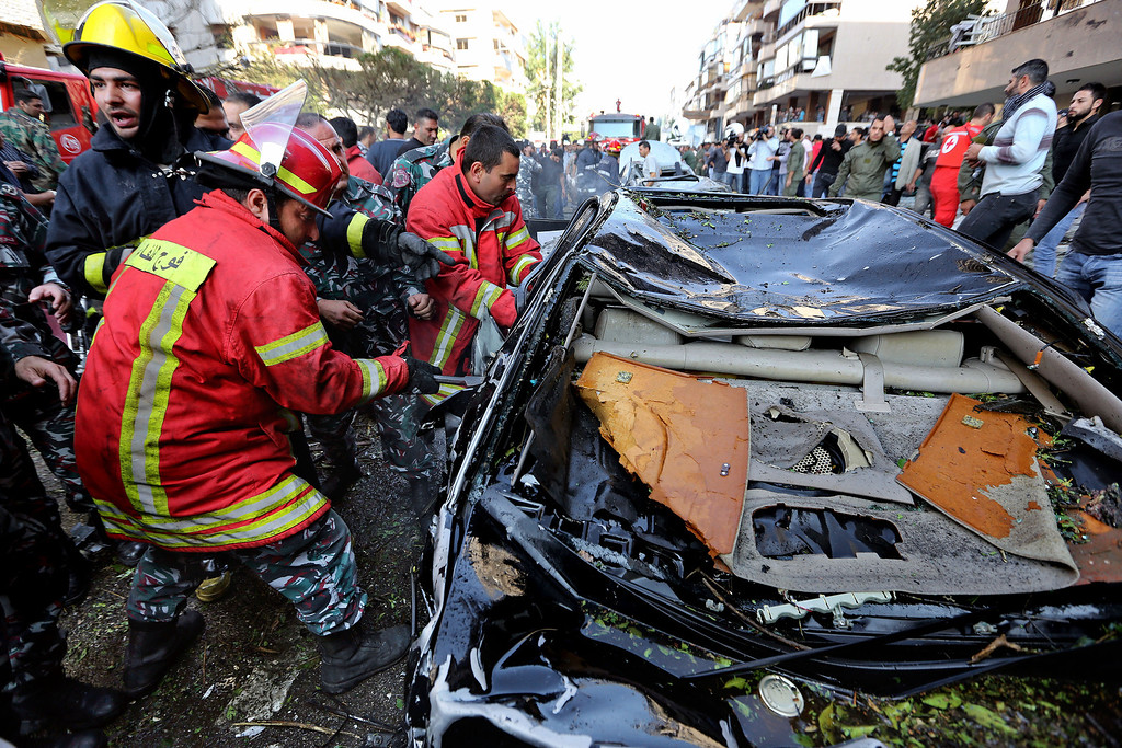 Description of . Lebanese Red Cross workers, pull a body from a car at the scene where two explosions have struck near the Iranian Embassy killing many, in Beirut, Lebanon, Tuesday, Nov. 19, 2013. (AP Photo/Bilal Hussein)