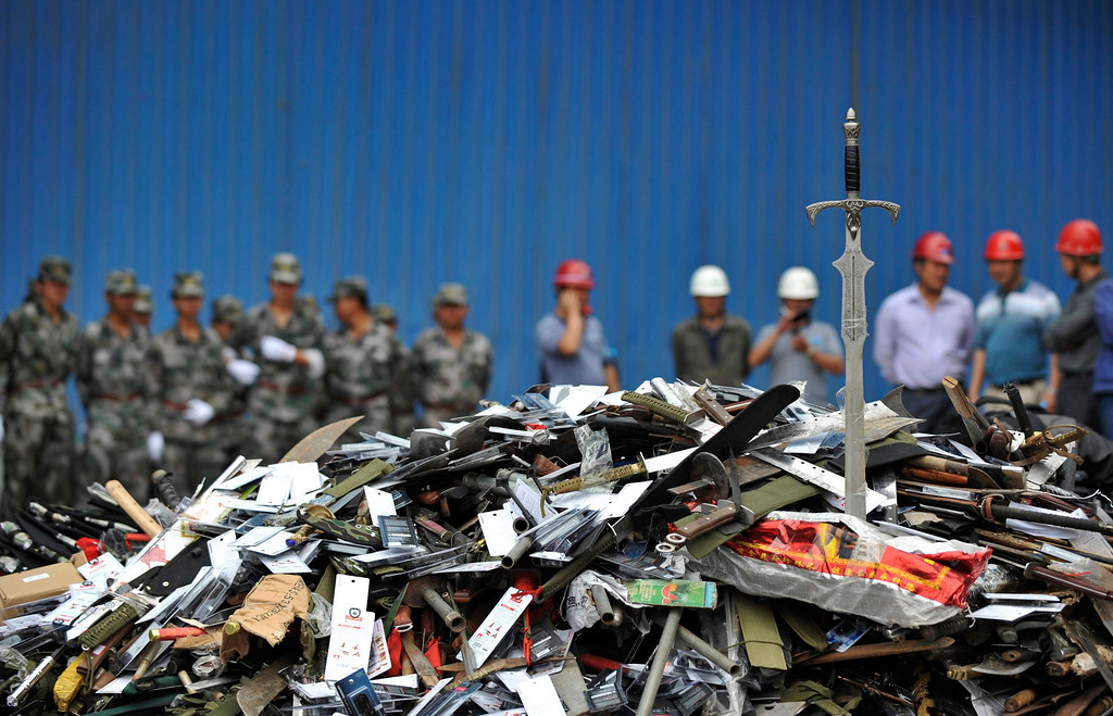 Description of . Workers stand guard as confiscated illegal weapons are collected to be destroyed at a steel plant on the outskirt of Kunming, Yunnan province June 12, 2012. Over 100,000 illegal firearms, replica toy guns, machetes and swords, which were collected by the Ministry of Public Security, were destroyed in 150 cities all over China on Tuesday morning, local media reported. REUTERS/Wong Campion