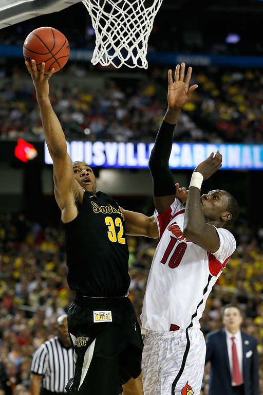 Description of . ATLANTA, GA - APRIL 06:  Tekele Cotton #32 of the Wichita State Shockers goes up for a shot against Gorgui Dieng #10 of the Louisville Cardinals in the first half during the 2013 NCAA Men's Final Four Semifinal at the Georgia Dome on April 6, 2013 in Atlanta, Georgia.  (Photo by Kevin C. Cox/Getty Images)