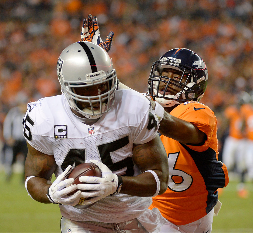 Description of . Oakland Raiders fullback Marcel Reece (45) catches a pass for a touchdown as Denver Broncos free safety Rahim Moore (26) tries to tackle him. The Denver Broncos took on the Oakland Raiders at Sports Authority Field at Mile High in Denver on September 23, 2013. (Photo by John Leyba/The Denver Post)