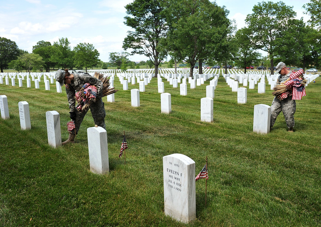 Description of . Staff Sergeant Joelle Monroe (L) of the Third US Infantry Regiment, The Old Guard, places flags in front of a graves at Arlington National Cemetery on May 23, 2013 in Arlington, Virginia ahead of Memorial Day. AFP PHOTO/Mandel NGAN/AFP/Getty Images