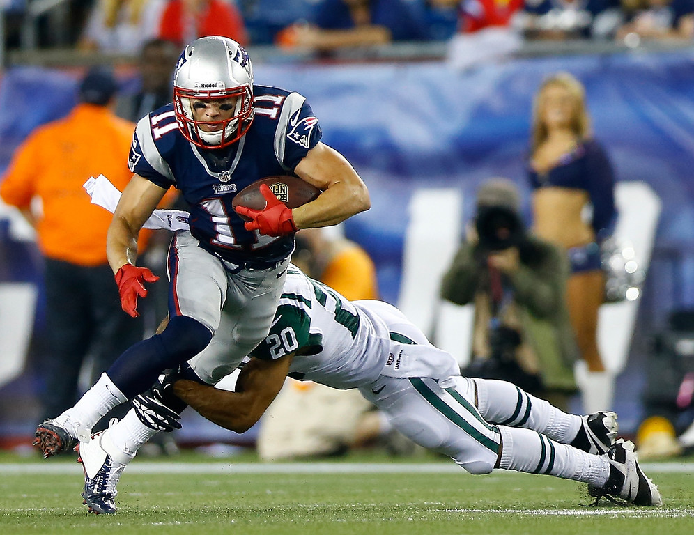 Description of . Wide receiver Julian Edelman #11 of the New England Patriots runs after a catch against cornerback Kyle Wilson #20 of the New York Jets in the first half at Gillette Stadium on September 12, 2013 in Foxboro, Massachusetts.  (Photo by Jared Wickerham/Getty Images)