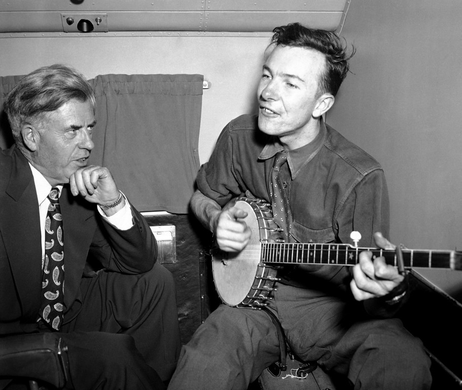 Description of . Henry A. Wallace, making a political tour of the south, listens to Pete Seeger, his banjo-playing singer, on a plane between Norfolk and Richmond, Aug. 28, 1948. (AP Photo)