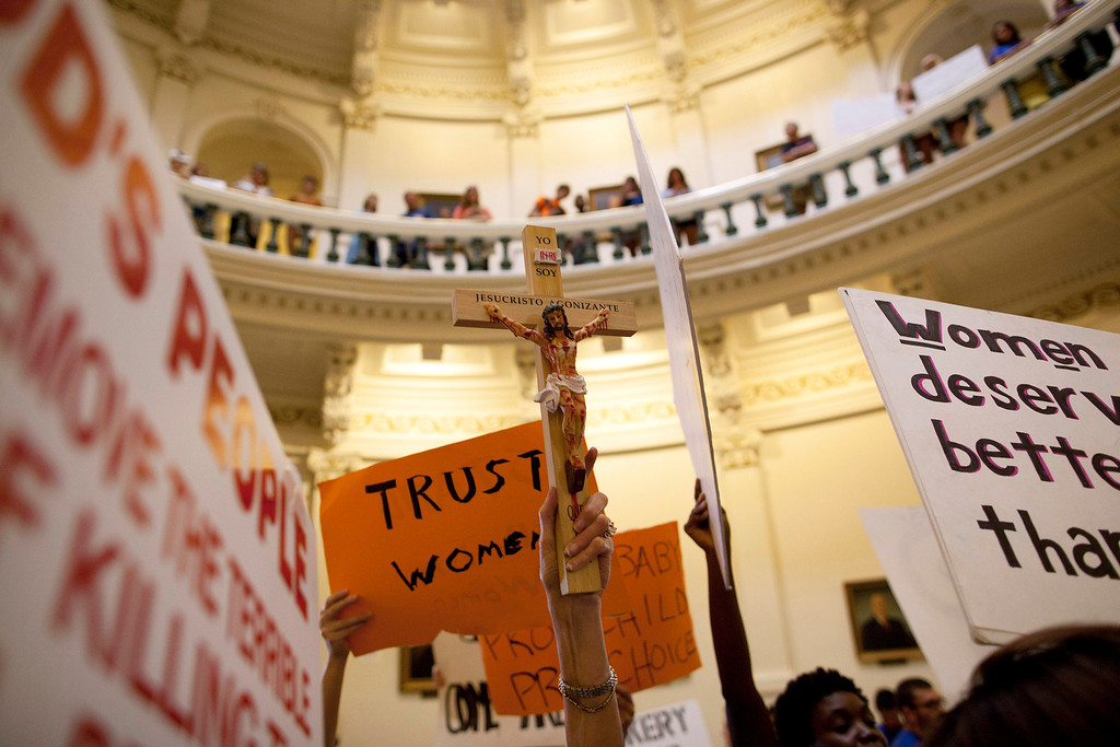 Description of . Opponents and supporters of abortion rights rally in the State Capitol rotunda in Austin, Texas on Friday, July 12, 2013. The Texas Senate convened Friday afternoon to debate and ultimately vote on some of the nation's toughest abortion restrictions, its actions being watched by fervent demonstrators on either side of the issue. (AP Photo/Tamir Kalifa)