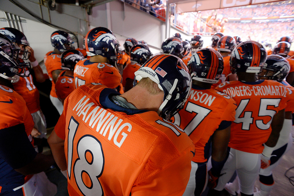 Description of . Denver Broncos quarterback Peyton Manning (18) waits to take the field before the Broncos' game agains the Baltimore Ravens. A lightning delay postponed the start of the game by about 30 minutes. (Photo by John Leyba/The Denver Post)