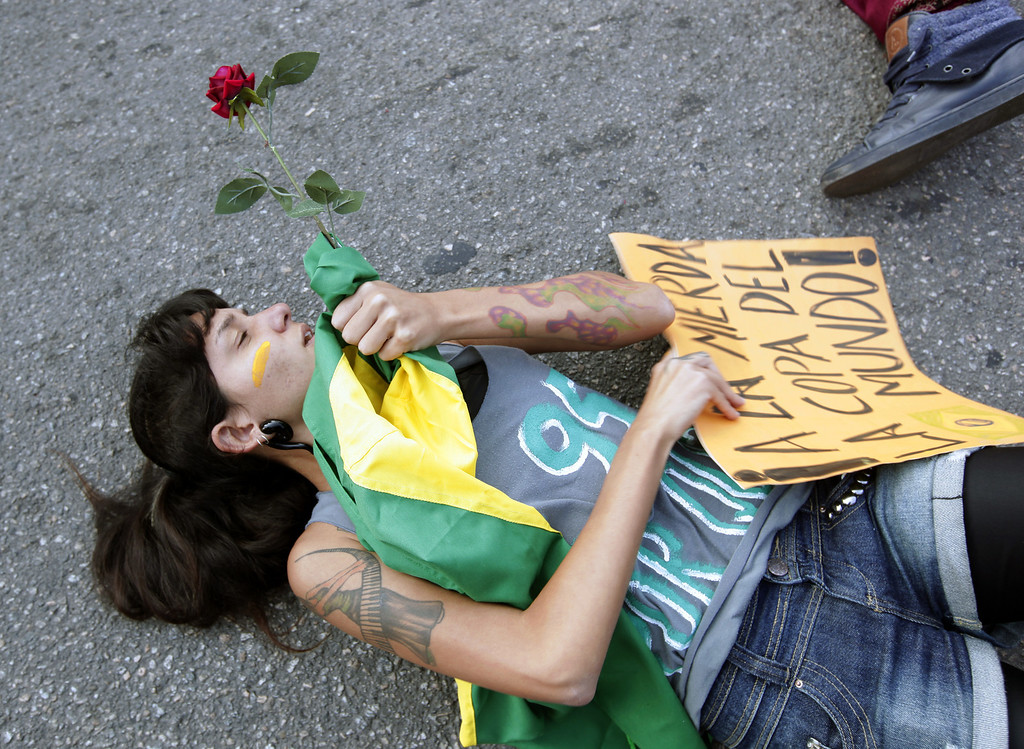 Description of . A protester lies on the ground in front of a police line in Rio de Janeiro, Brazil, Sunday, June 16, 2013. Brazilian police dispersed a small protest against a public transport fare hike that broke out in front of Rio de Janeiro's Maracana stadium ahead of the Mexico-Italy soccer match during the Confederations Cup. (AP Photo/Bruno Magalhaes)