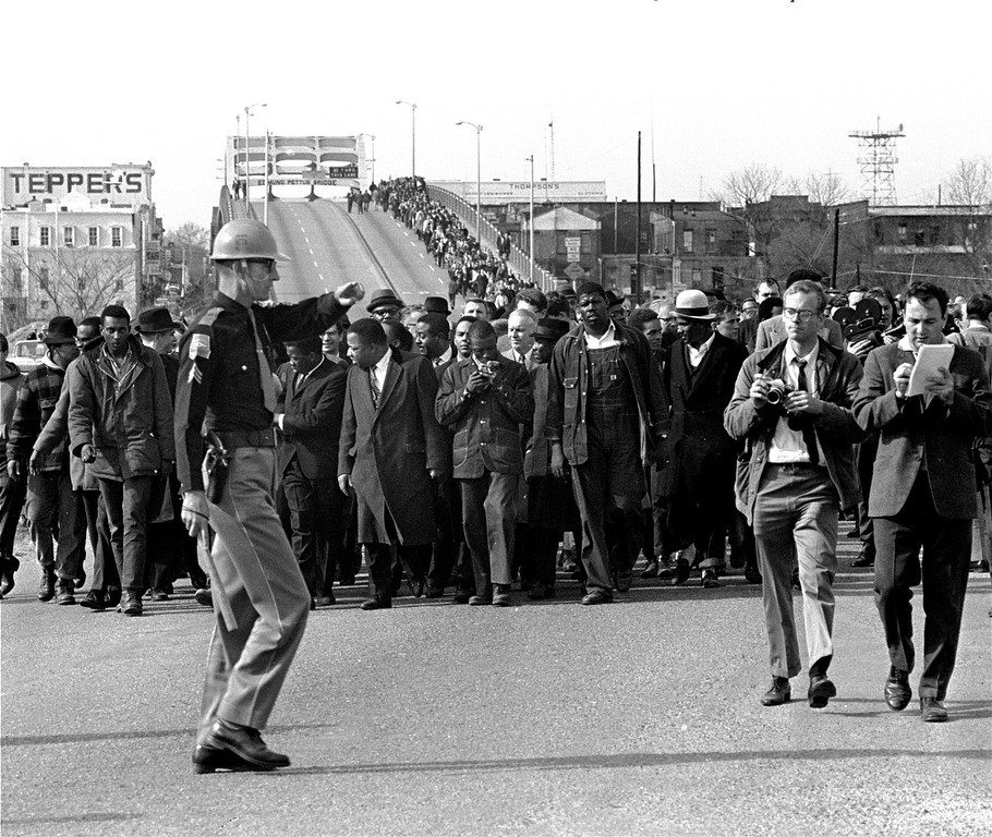 Description of . Demonstrators, including Dr. Martin Luther King, Jr., stream over an Alabama River bridge at the city limits of Selma, Ala., in this March 10, 1965 file photo, during a voter rights march. (AP Photo, File)