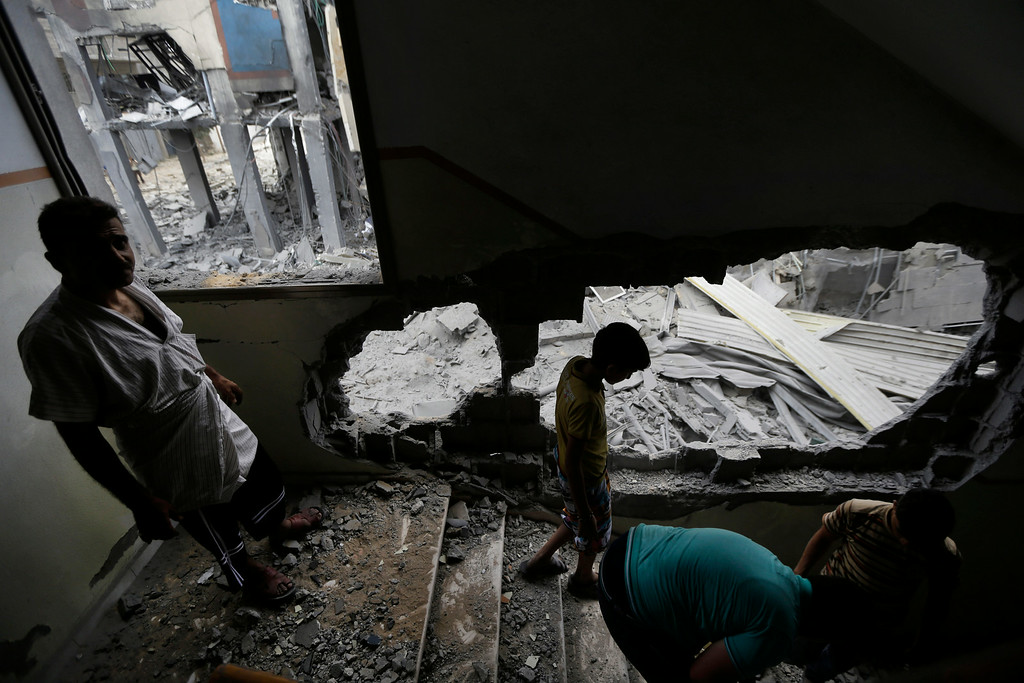 Description of . Palestinians clear the debris as they inspect the damage of the offices of the Hamas movement's Al-Aqsa satellite TV station, in Gaza City, northern Gaza Strip, destroyed by an Israeli strike, Tuesday, July 29, 2014. (AP Photo/Lefteris Pitarakis)