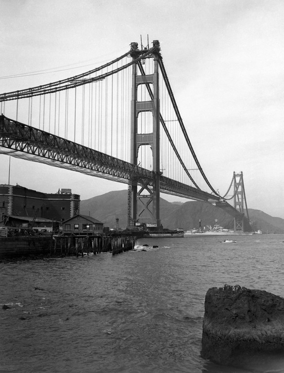 Description of . A view of the Golden Gate Bridge, while under construction, with a warship seen passing underneath on its way to the opening of the Oakland Bay Bridge, on Nov. 12, 1936. (AP Photo)